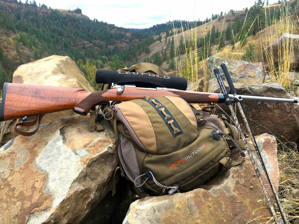 A backcountry hunting backpack and a rifle leaning on a pile of boulders.