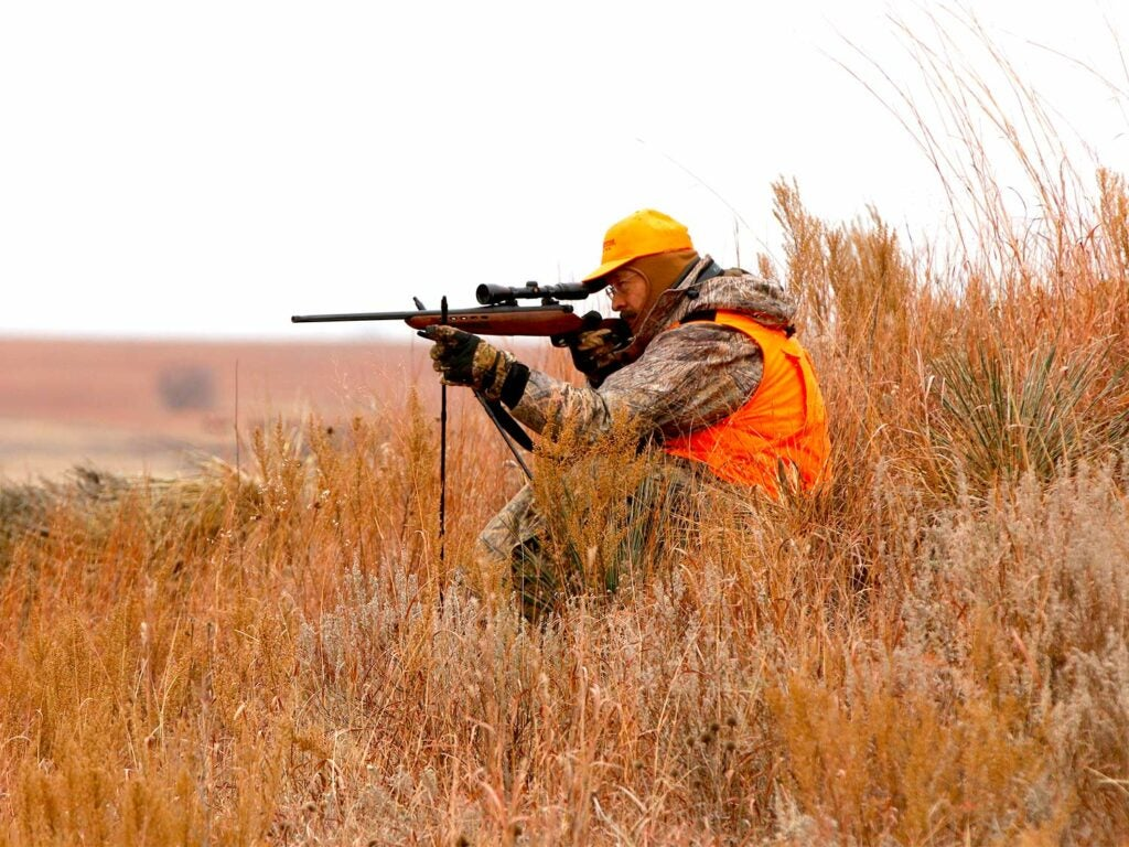 A hunter in camo and orange aims a rifle in a field.