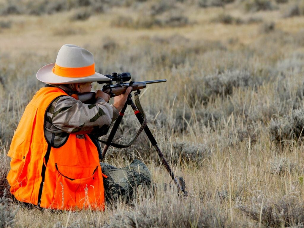 A hunter in orange and camo aims a rifle in a field.