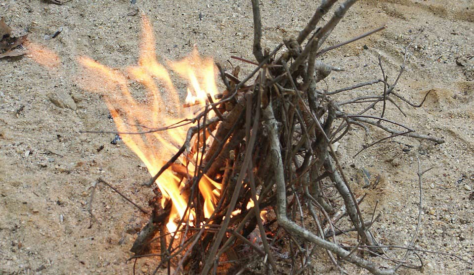 A bundle of sticks in the sand on fire.