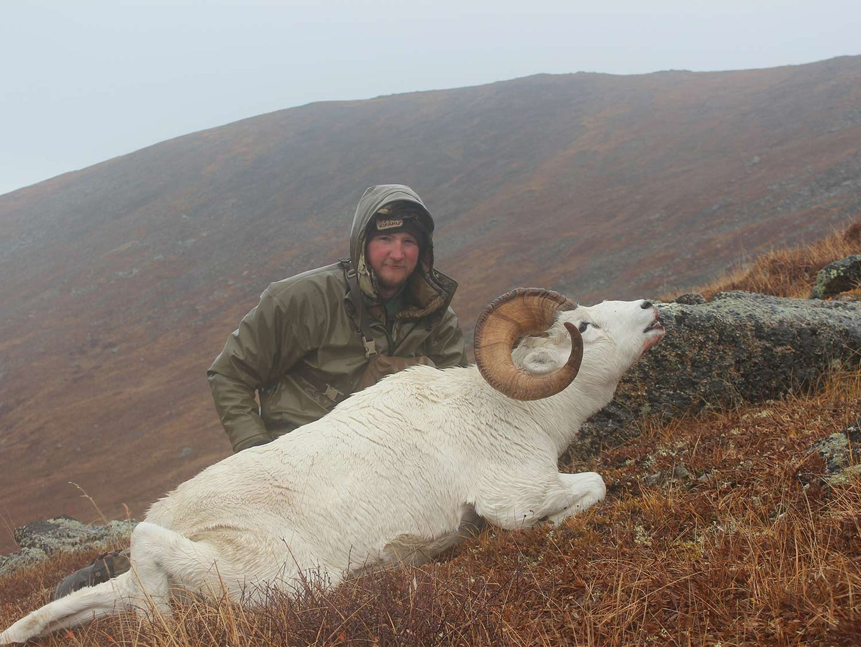 A hunter kneeling behind a white sheep.