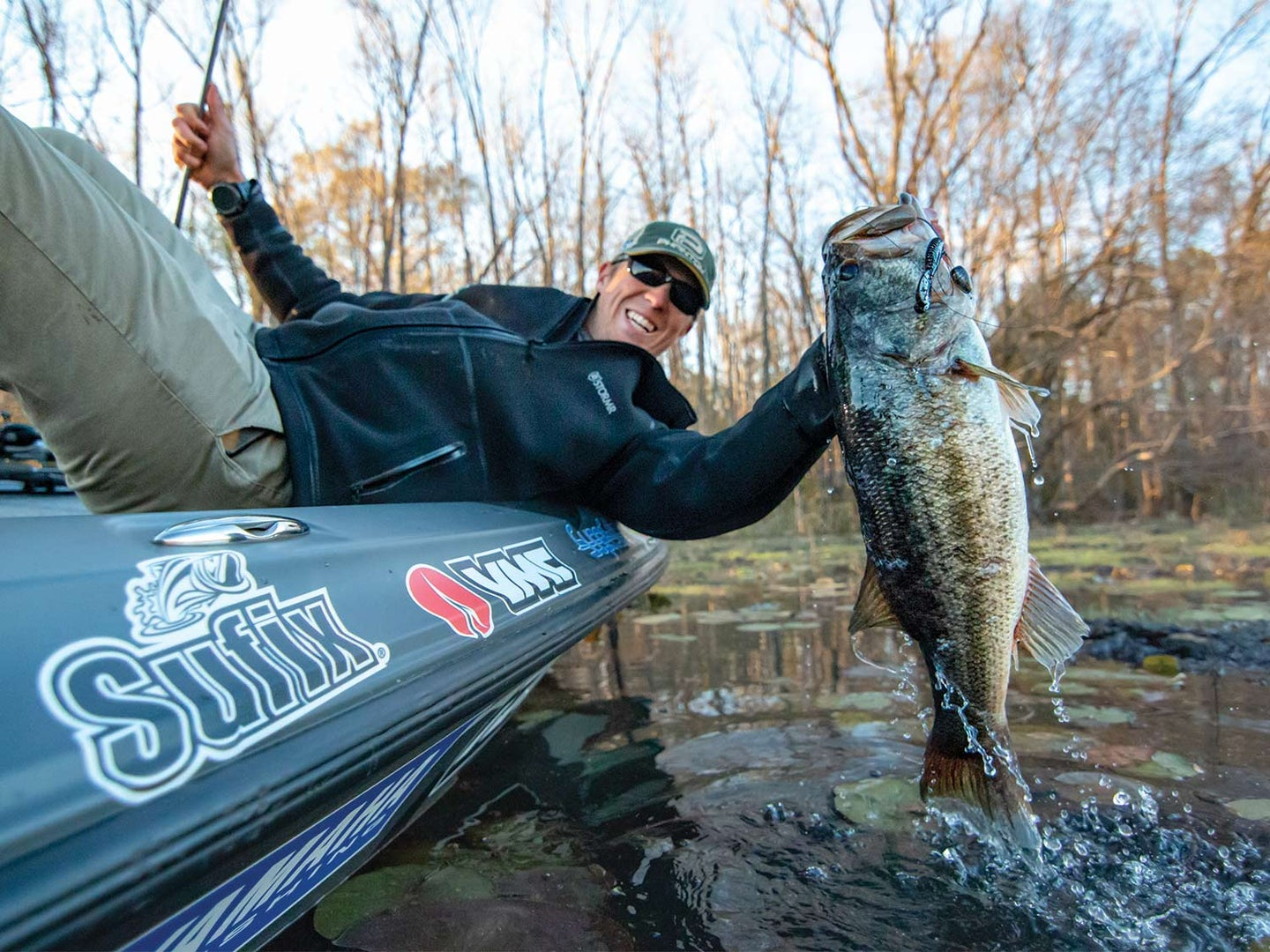 Patrick Walterns on the side of a boat hoisting a largemouth bass from the water.