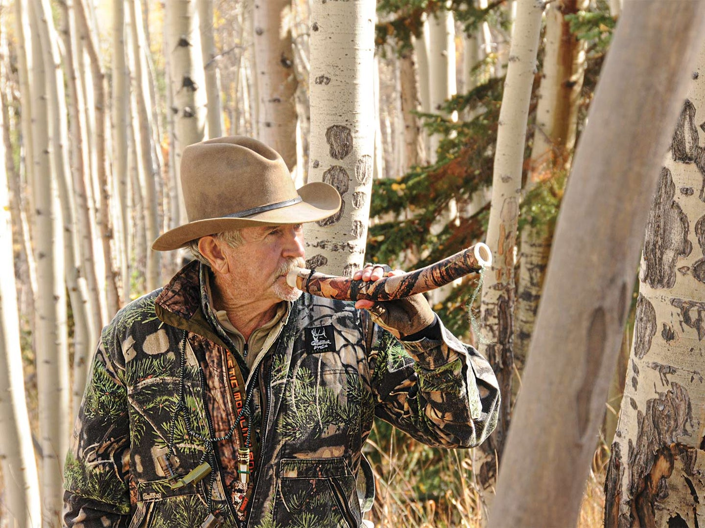 A hunter in camo and cowboy hat using a hunting call.
