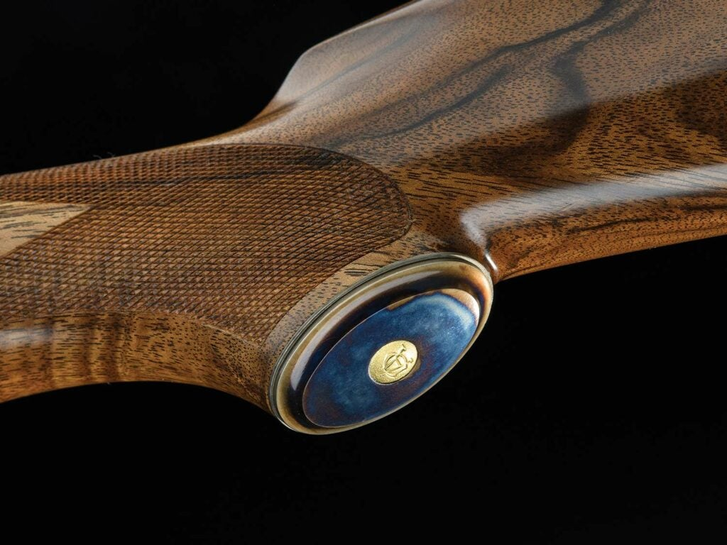 A case-colored grip cap on a rifle stock.