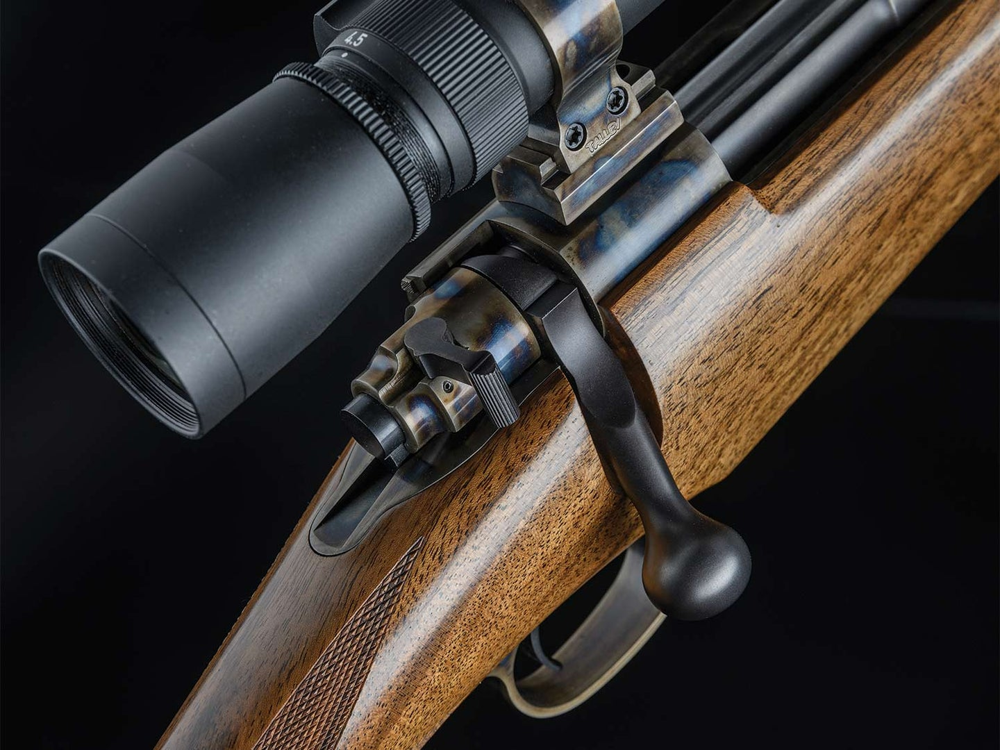 Closeup details of a scoped rifle on a black background.