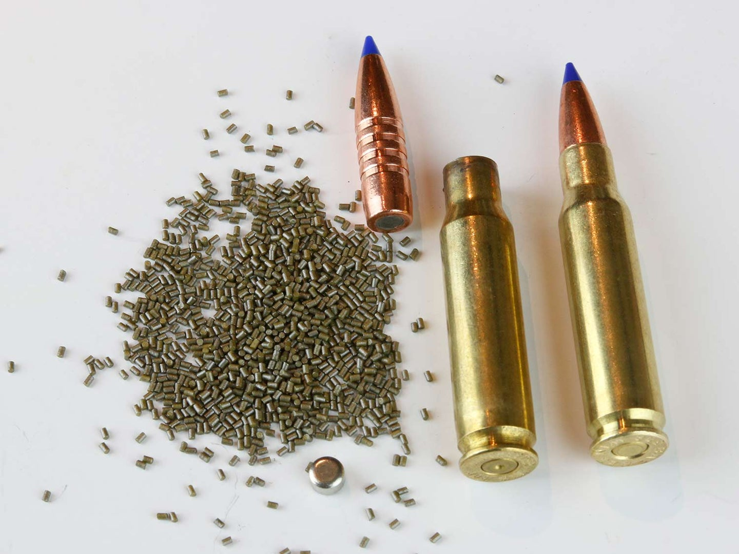 A rifle cartridge next to an emptied cartridge and bullet and gunpowder.