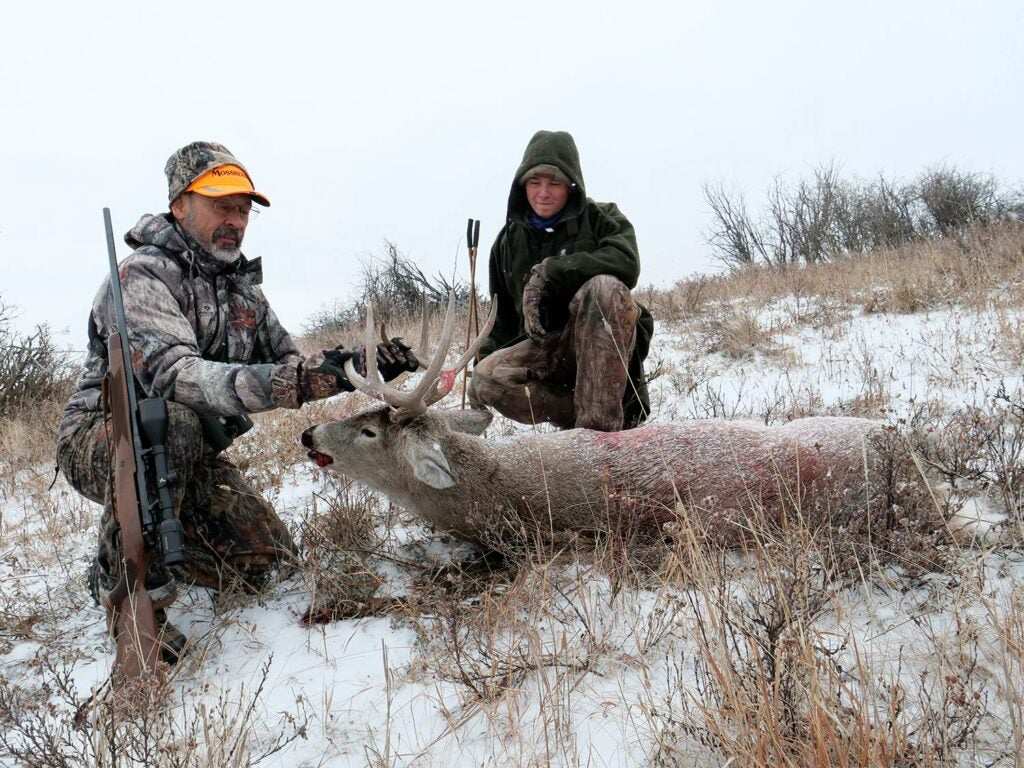 Two hunters kneeling behind a whitetail buck in the snow.