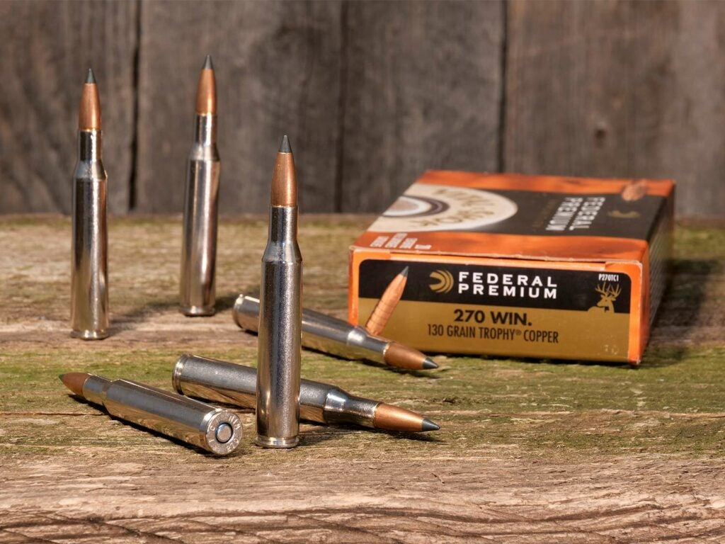 A box of federal premium rifle ammunition laying and standing on a table.