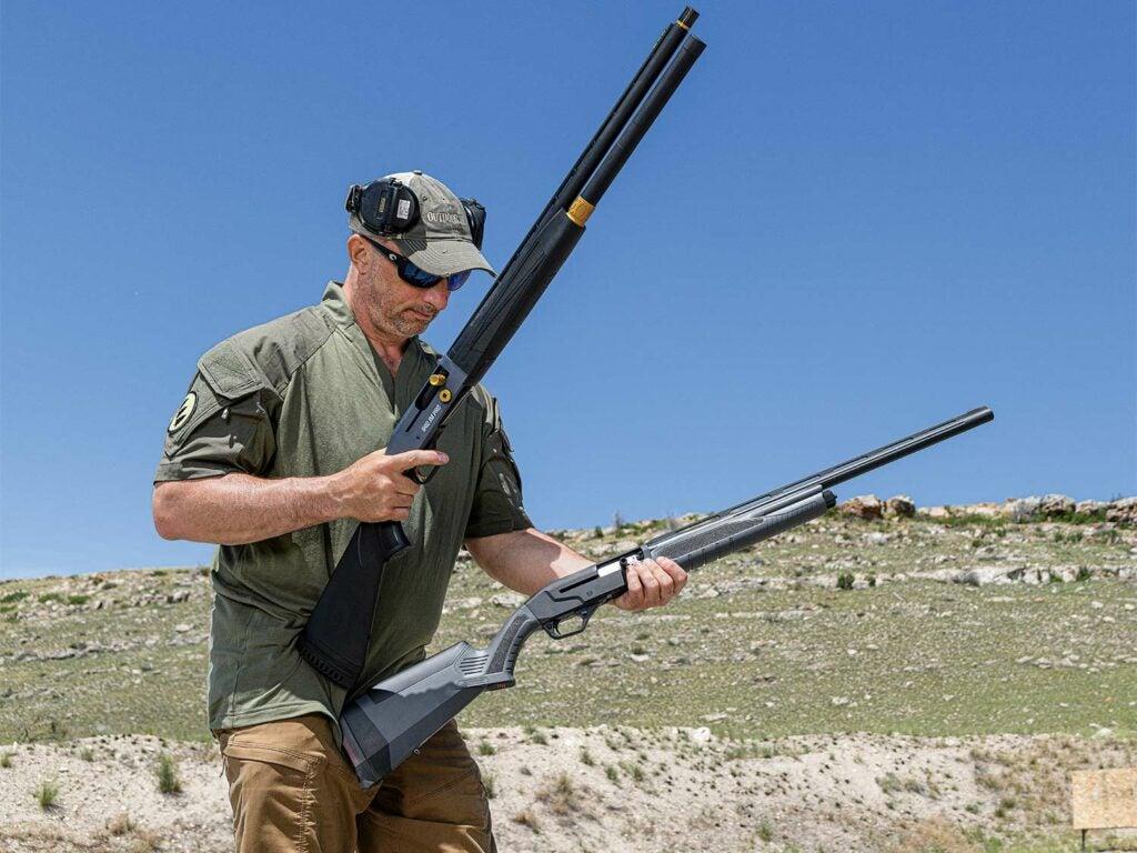 A man holding up two shotguns at a shooting range.