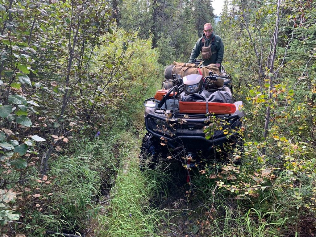 A man on a four-wheeler equiped with brush bumpers.