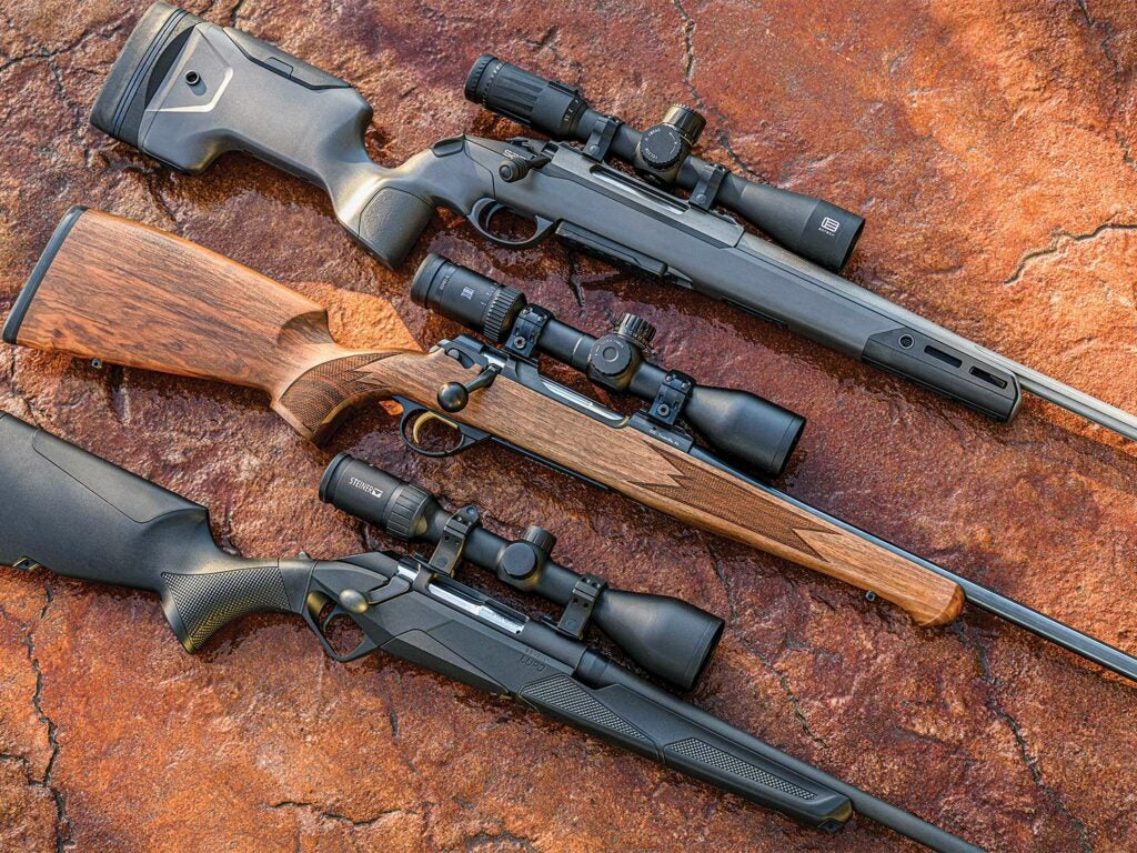Three rifles arranged and rested on a large flat red stone.