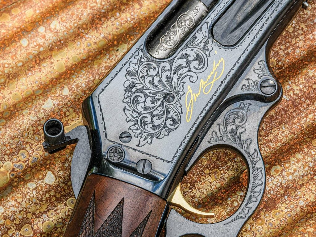 Close up detailings of engravings and design on a metal Marlin Anniversary Edition rifle.