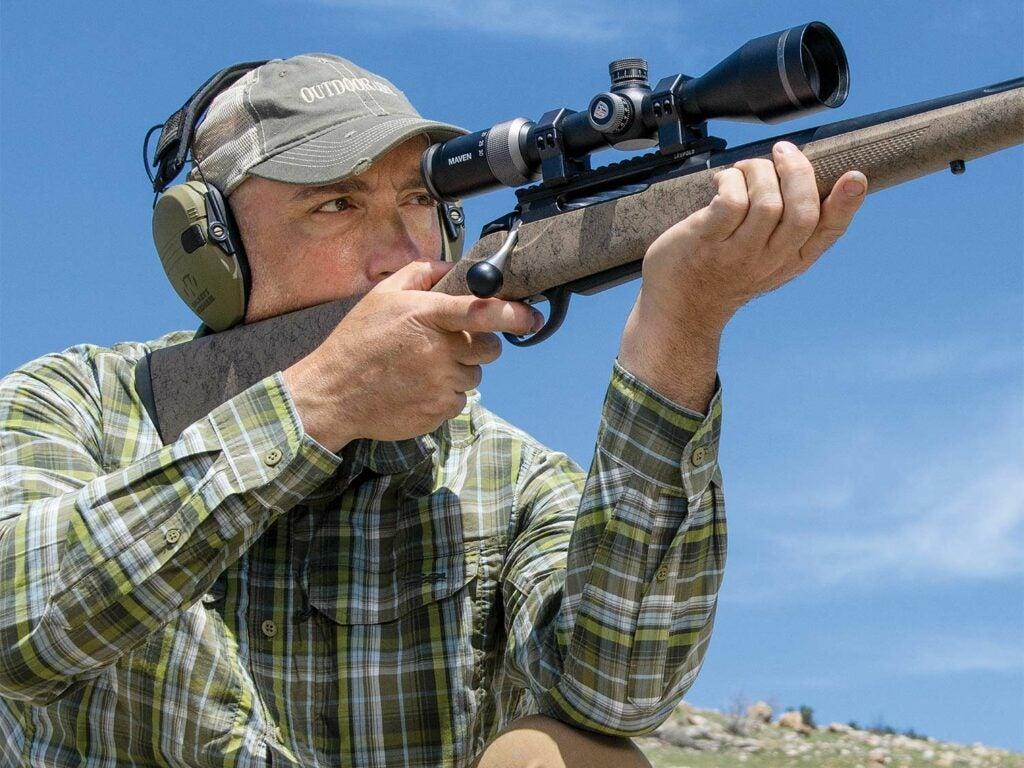 A man in a cap aims a Tikka T3x Lite Roughtech rifle during a gun test.