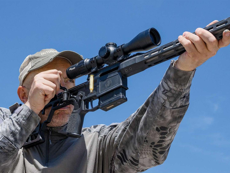 A man in a cap aims a Sig Sauer SIG Cross rifle during a gun test.