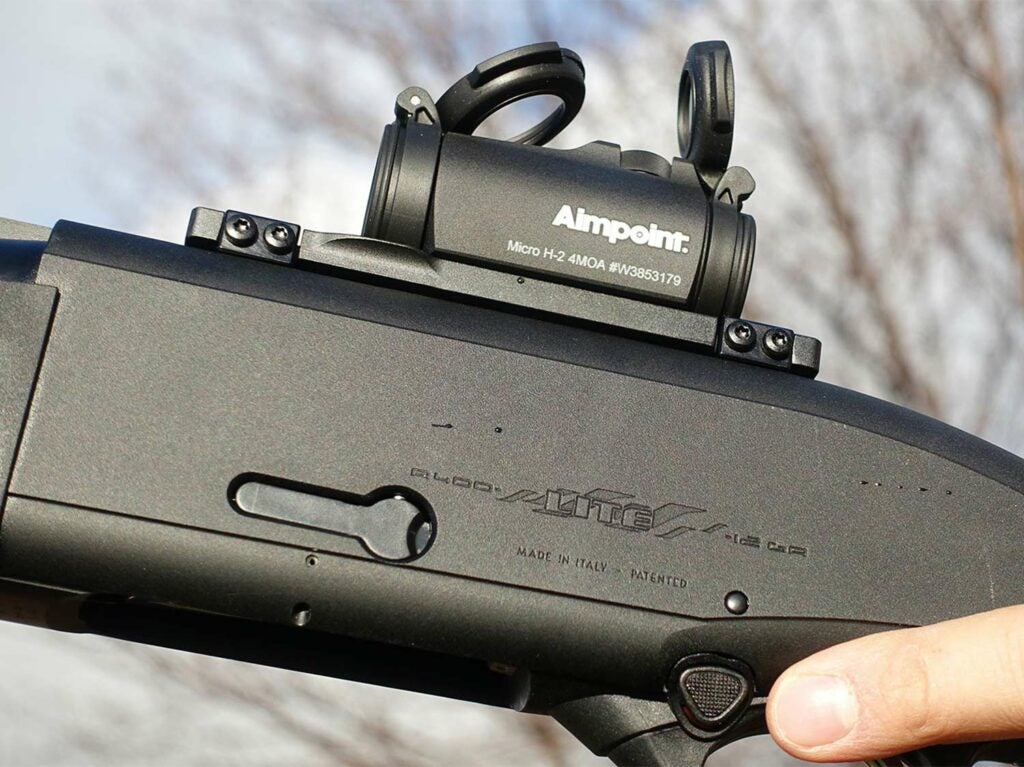 A red-dot sight mounted on a shotgun.