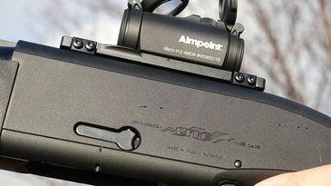 A red-dot sight mounted on a shotgun.