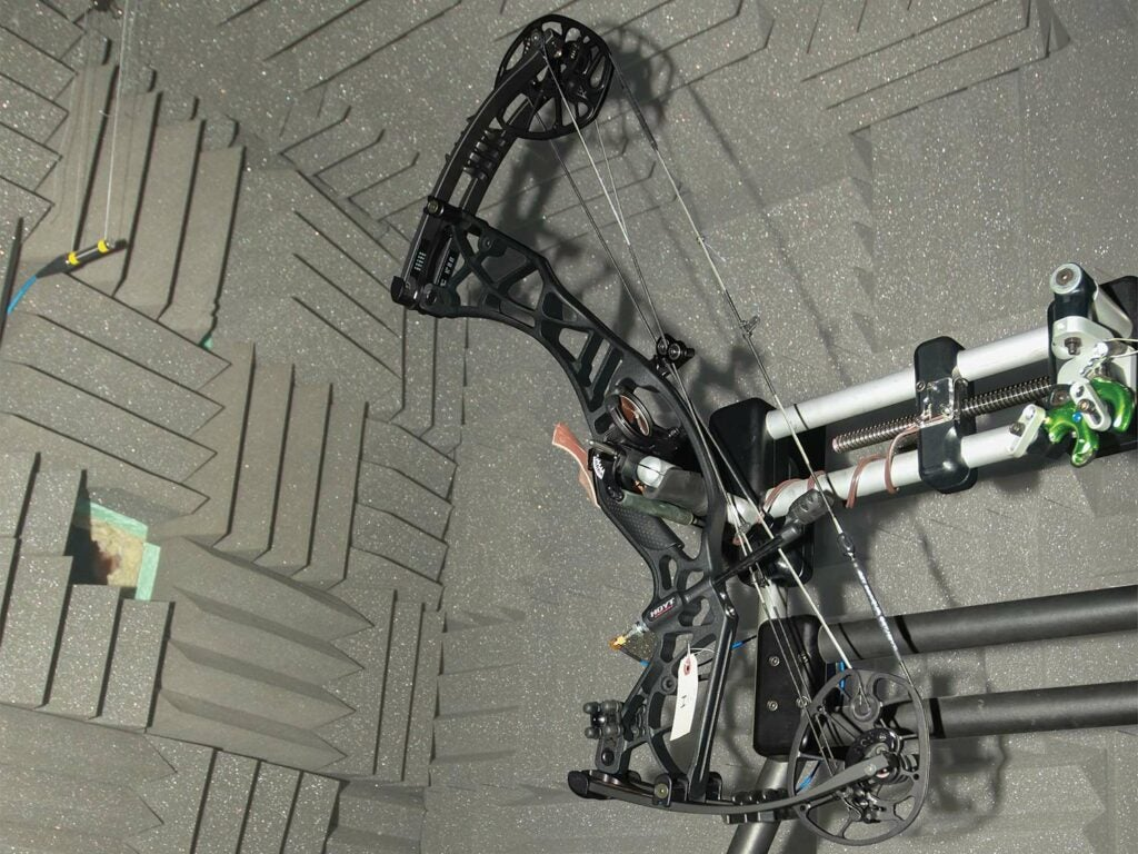 A compound bow being tested in a anti-echo chamber.