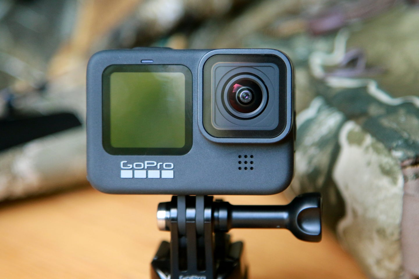 black gopro hero9 action camera with front lens and camo in the background