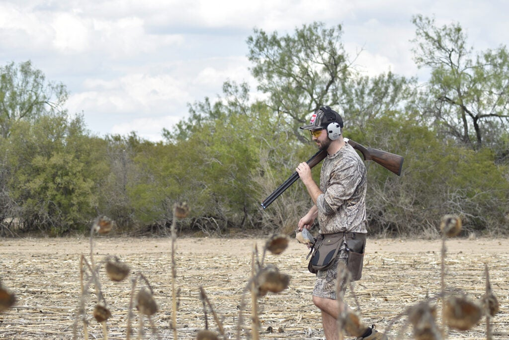 A hunter walks through a large open field with a shotgun over his shoulder.