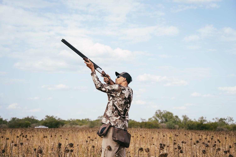 A male hunter aims a shotgun in the air.