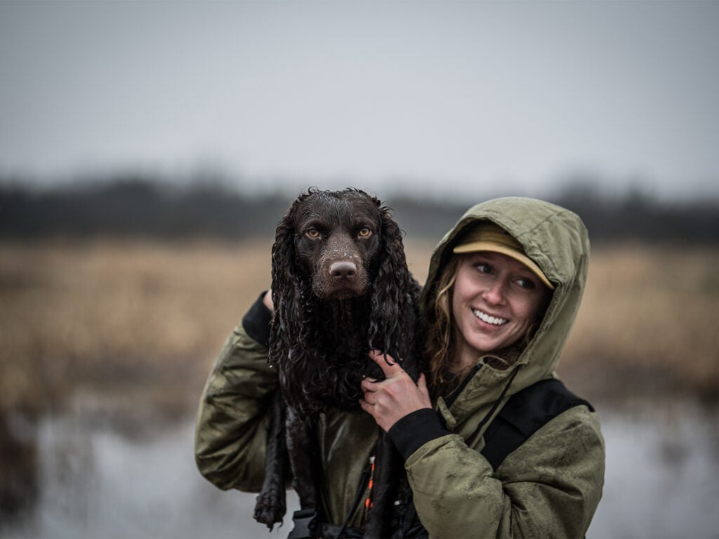 A woman hunter holding up a hunting dog.