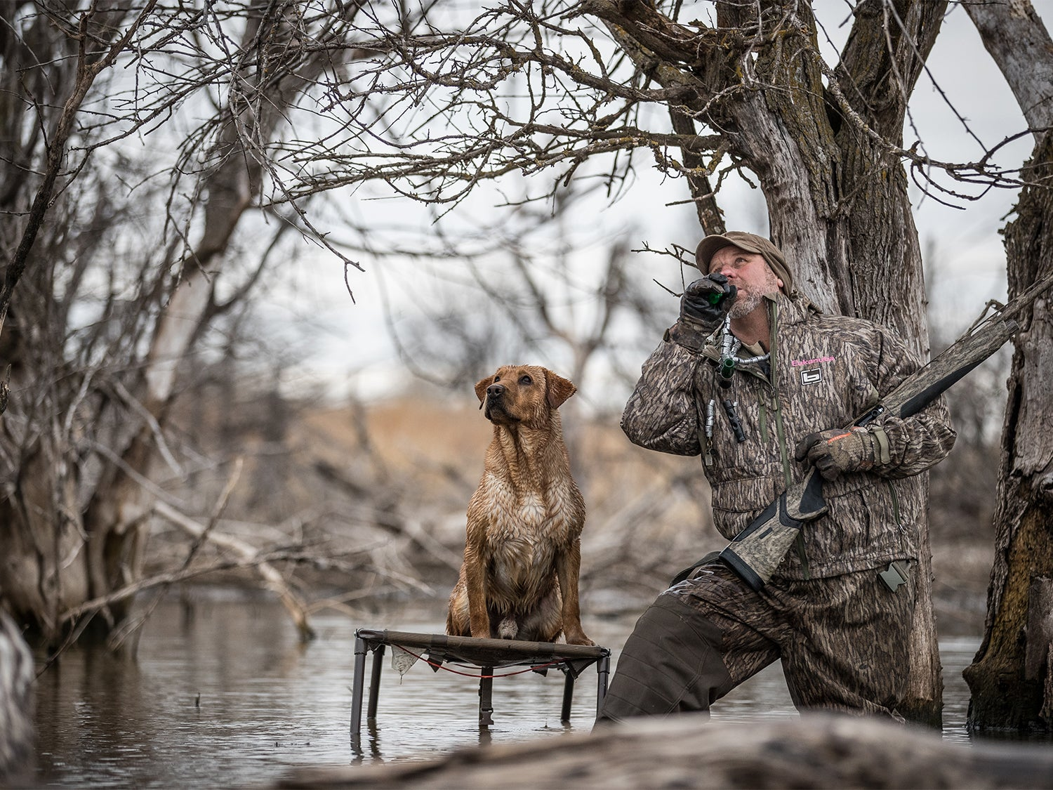 A hunter wading in the water on a duck call.