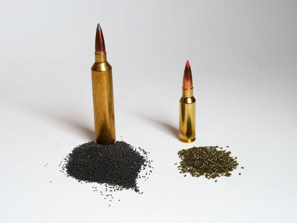 Two rifle bullets and their gun powder load poured out next two them.
