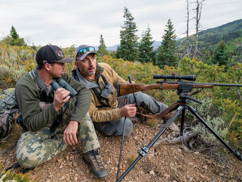 Two hunters sit on a hillside with a rifle on a tripod and scout through binoculars.
