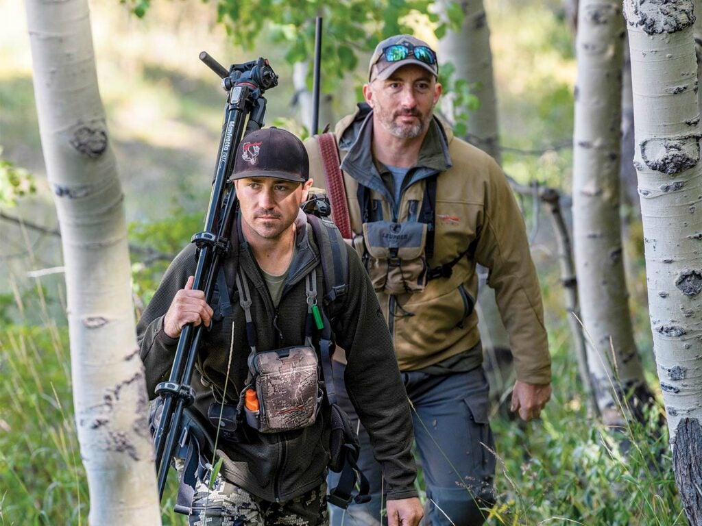 Two hunters hike through the woods and carry their gear with them.
