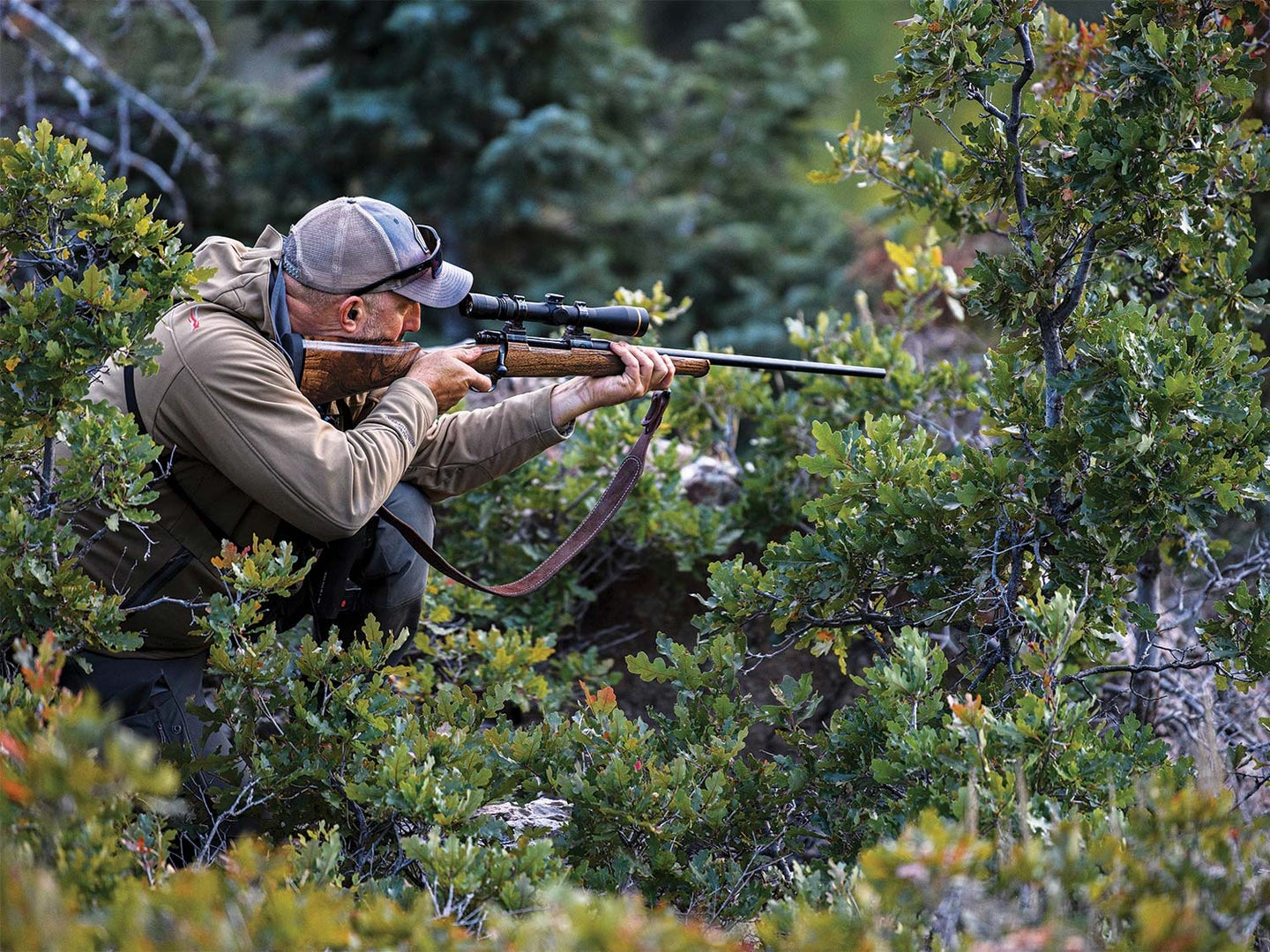 A hunter stands amongst brush and cover while looking through a riflescope and holding a rifle against his shoulder, ready to fire.