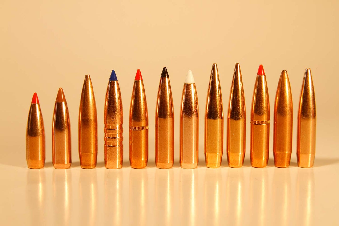 A lineup of several rifle ammunition tips on a table.