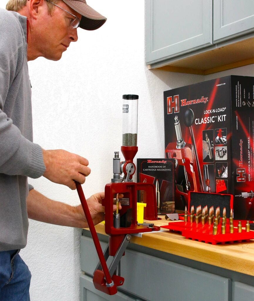 A man operates a custom handloading machine designed for dropping gunpowder into small cyclinders of rifle ammunition cartridges.