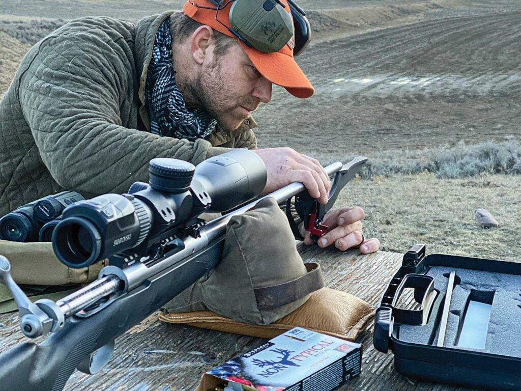 A man adjusts a MagnetoSpeed chronograph on a riflescope.