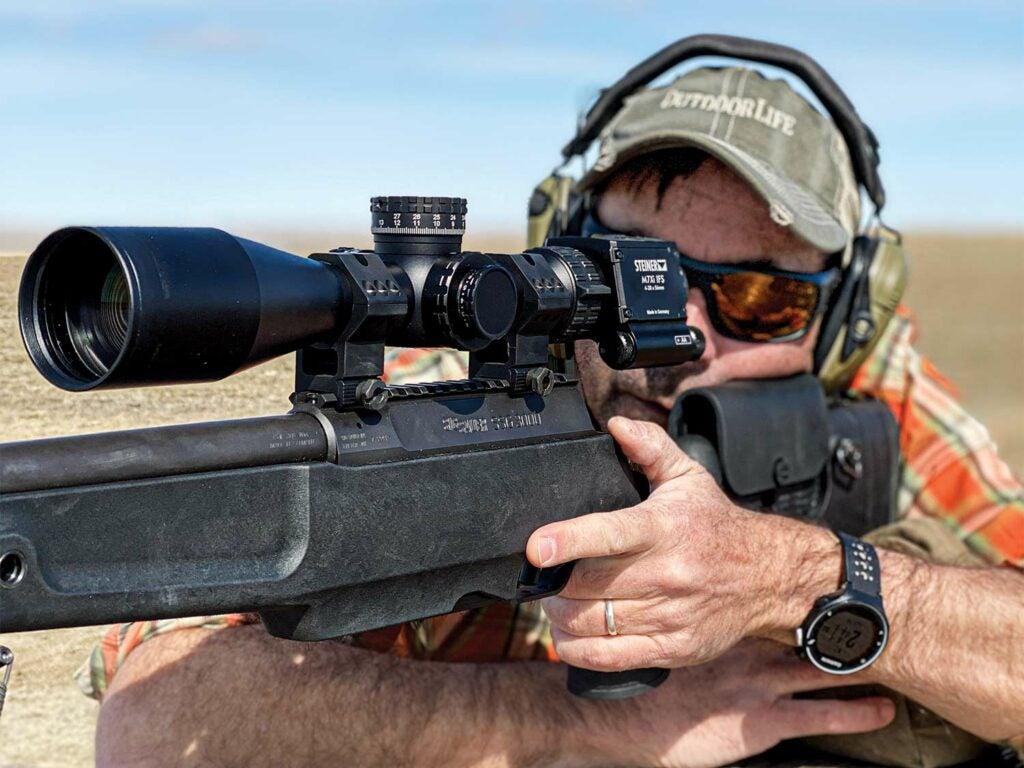A man in a ball cap aims a rifle and looks through the rifle scope.