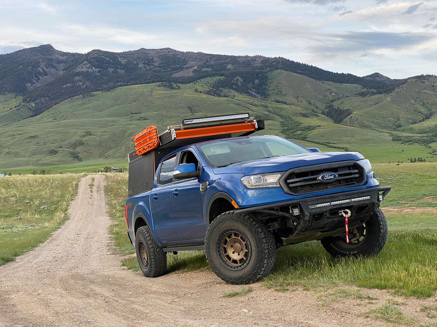 A blue ford pickup truck outfitted with custom attachments and gear.