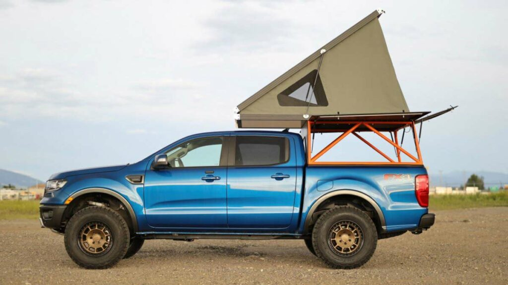 A blue Ford pickup truck with a truck-bed mounted camping tent.