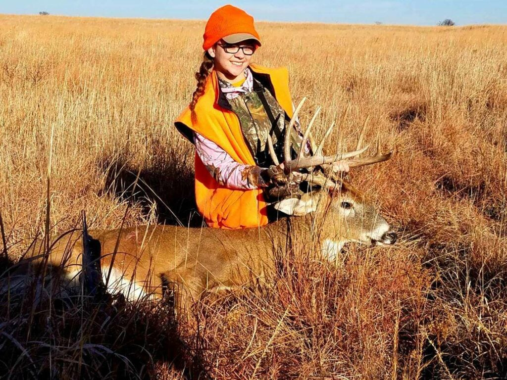 A young girl clad in hunter orange kneels behind a whitetail buck in a large open field and holds its head up by the antlers.