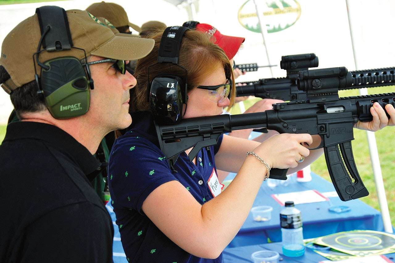 A woman holds a rifle to her should while taking aim, as an instructor stands beside her offering tips. Both are wearing shooting protection gear.