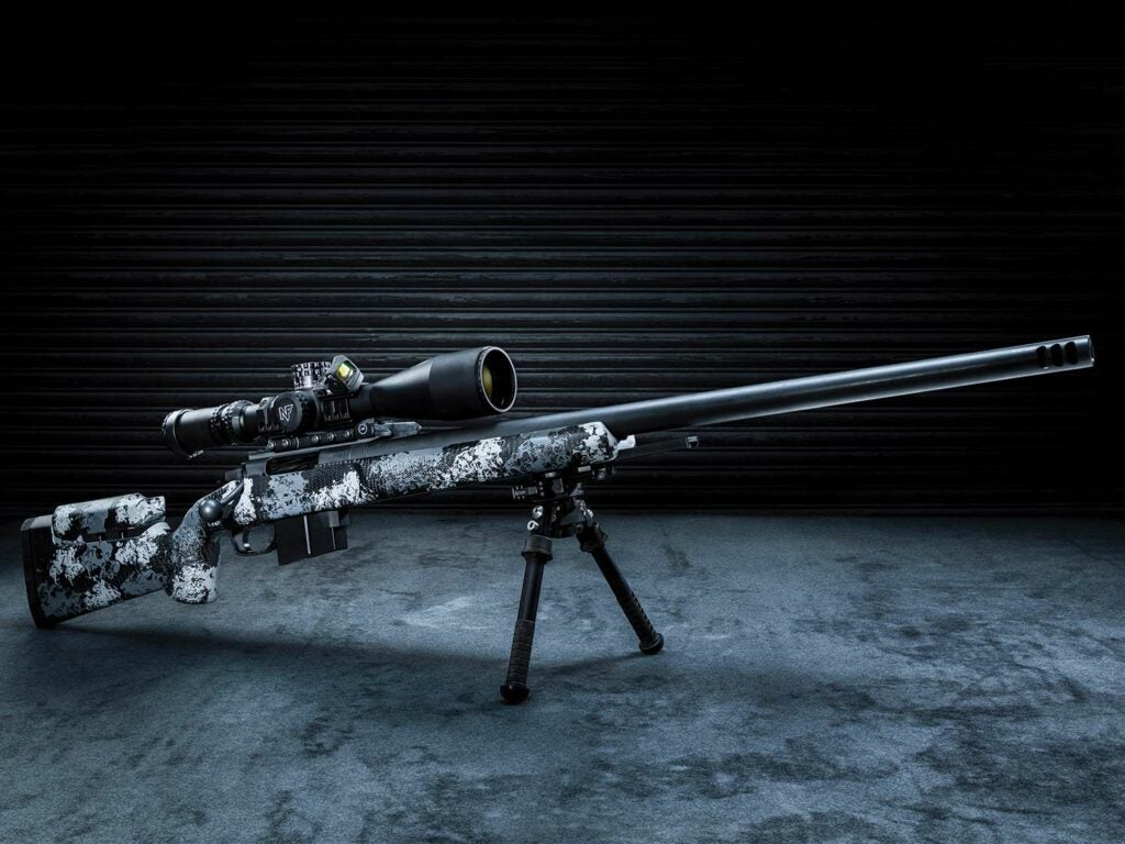 A black and grey camo-patterned rifle equipped with a riflescope and resting on shooting bipods.
