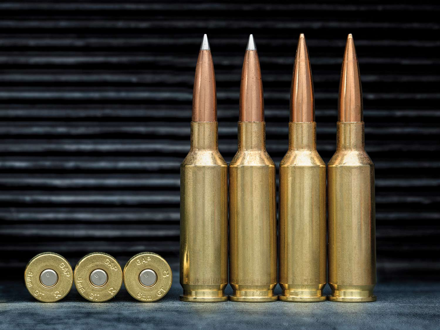 A lineup of rifle cartridges against a ridged black background.