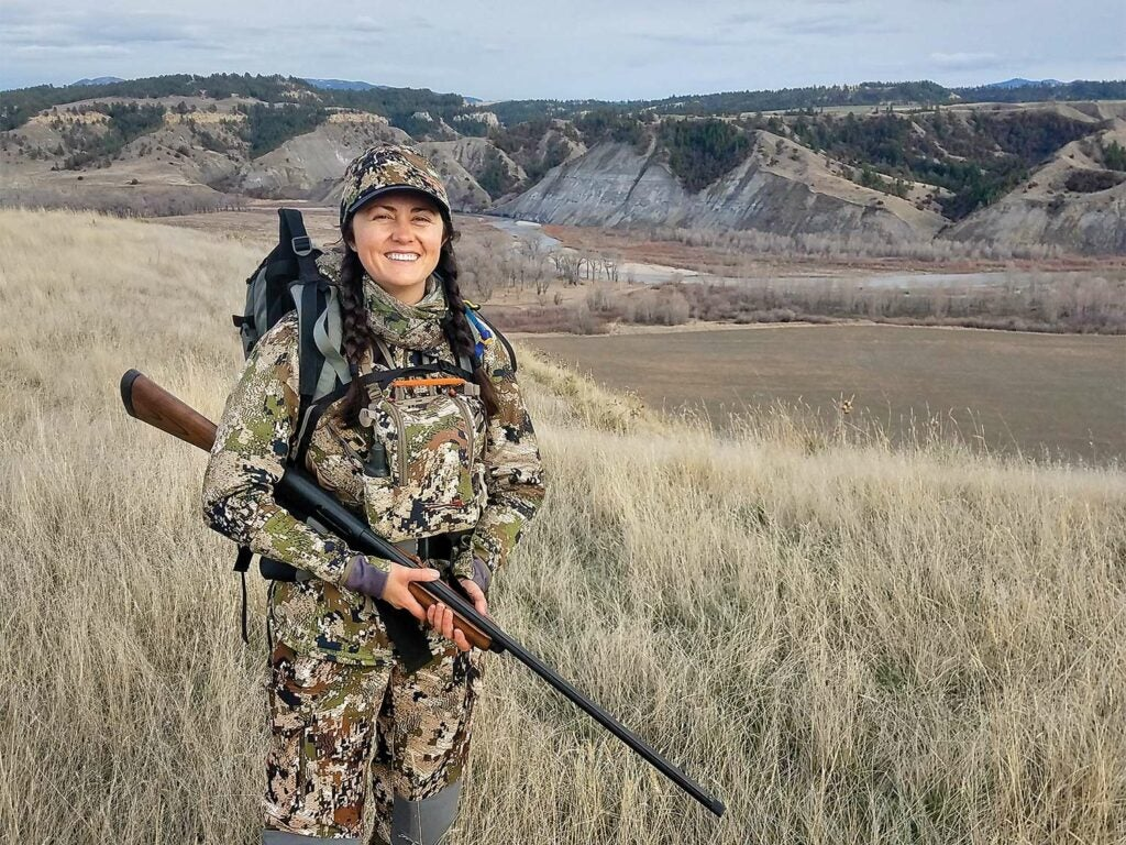 A woman wearing full camo and holding a shotgun stands in a large midwestern plain with hills and mountains in the background.