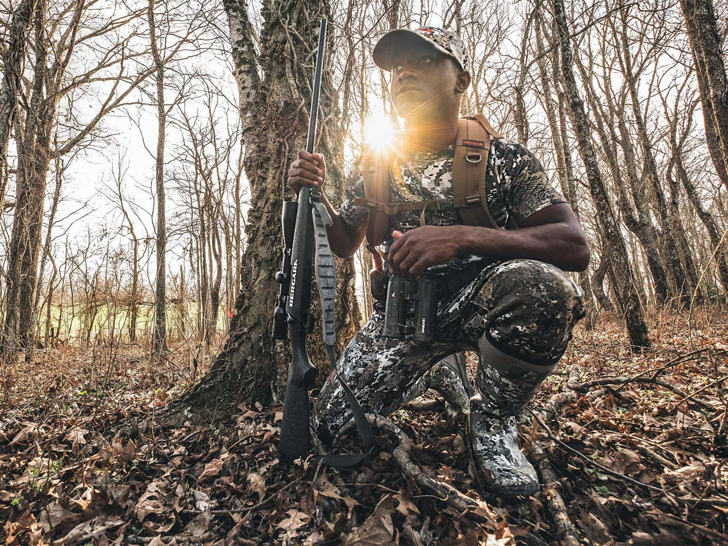 A young deer hunter kneels in the woods wearing full camo gear and holding a rifle in one hand.