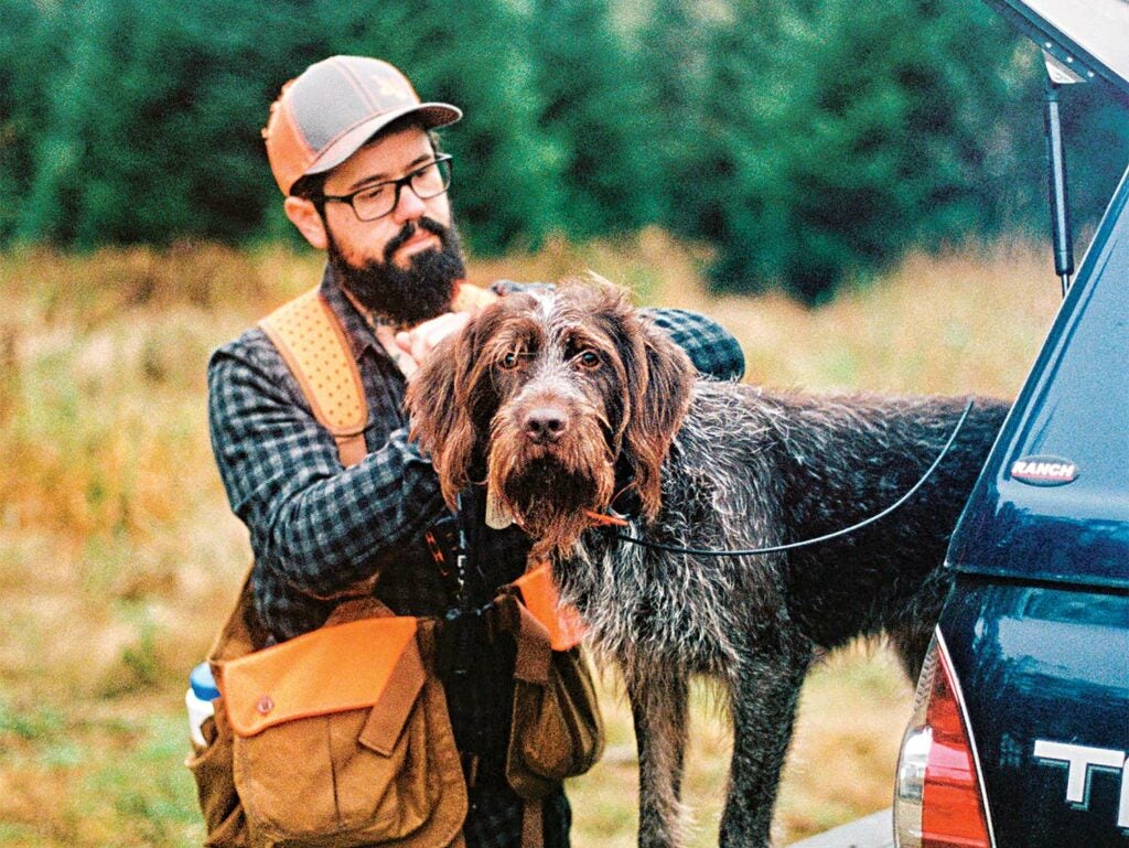 A bearded man wearing glasses and orange reflective hunting gear collars his hunting dog that is standing in the bed of the hunter's truck.