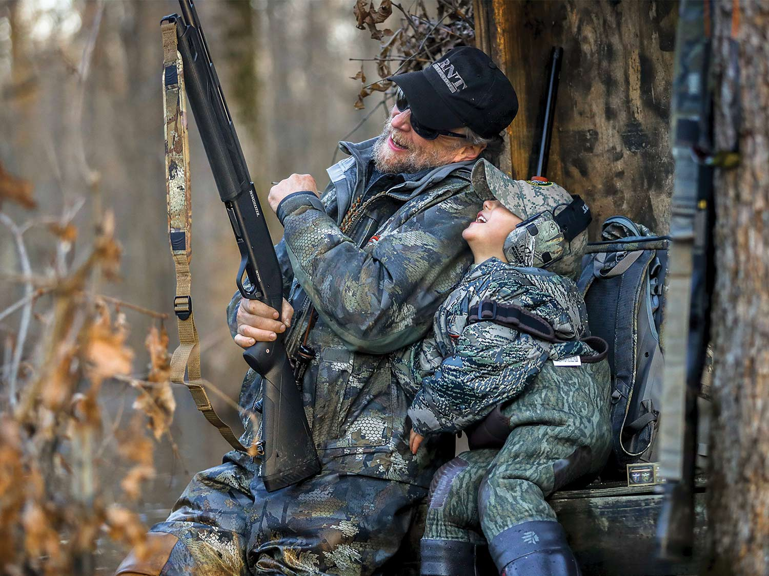 An elderly gentleman holding a rifle laughs and smiles with his grandchild in a tree stand.