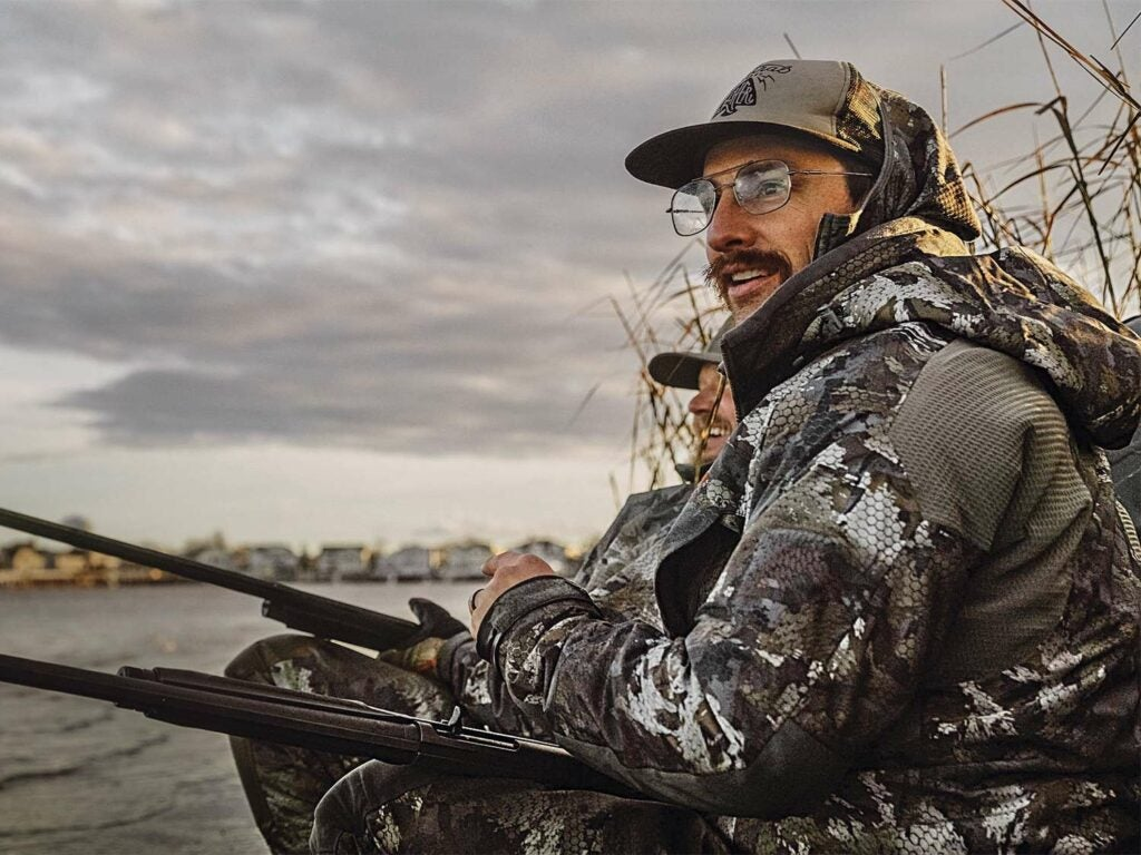 A man in glasses and wearing full camo sits by the waterside with a shotgun in his lap.