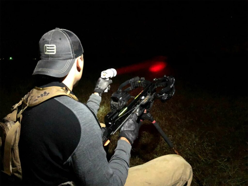 A man in a backwards cap uses a red flashlight at night.