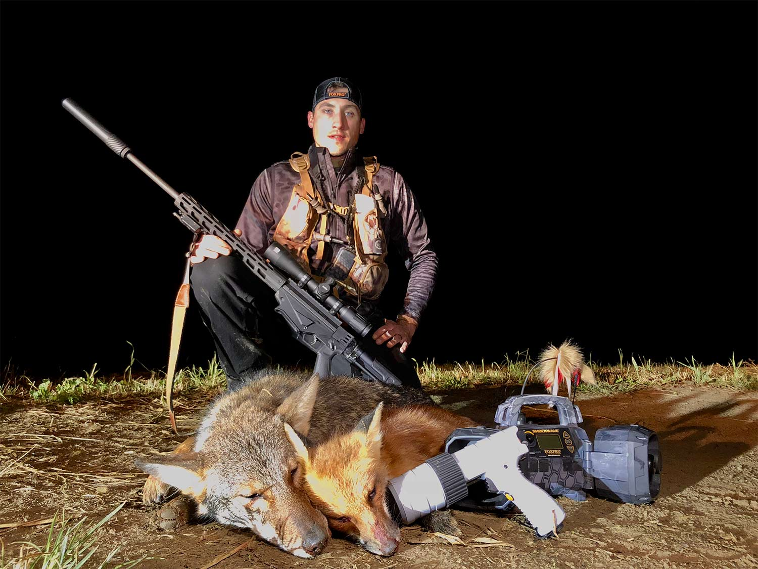 A hunter takes a knee behind a dead coyote and a fox at night with a rifle over his raised knee.