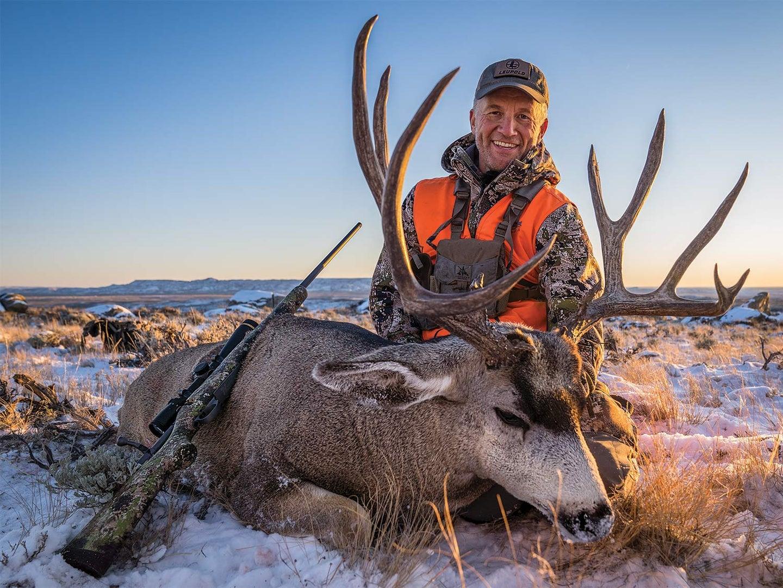 A hunter smiles and kneels behind a large mule deer in the snow.