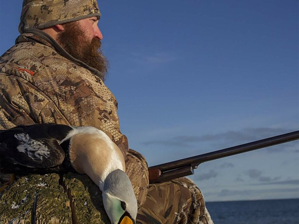 A hunter sits with a shotgun on his lap next to a duck.