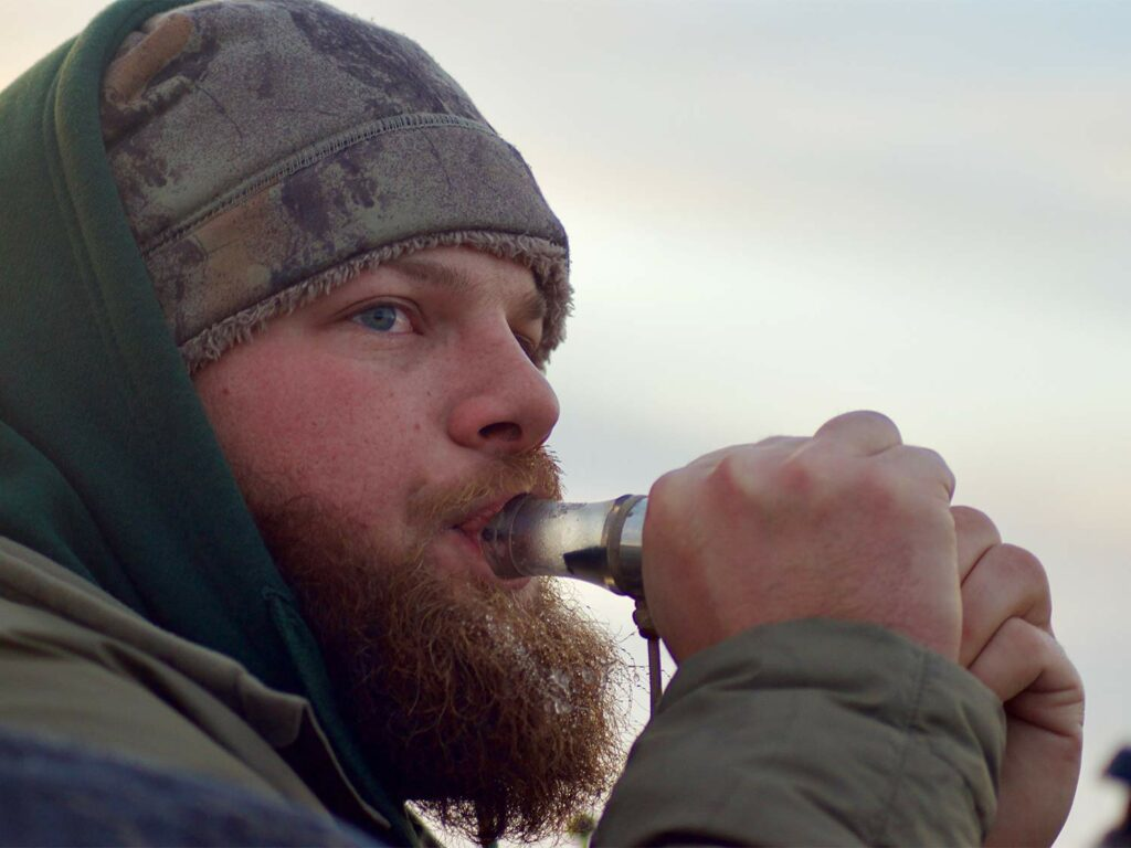 A bearded man uses a bird call.